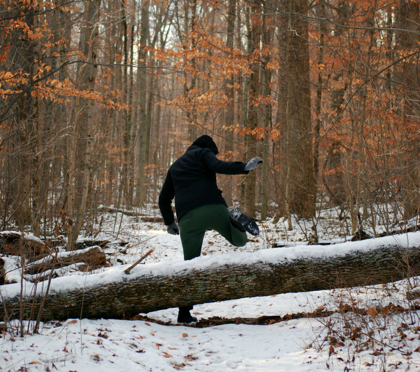 A man dressed warmly steps over a log that's fall over a snow-covered trail.