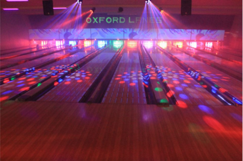 A bowling alley with lots of multi-colored lights shining on the lanes.