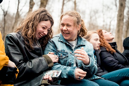 Two girls laugh while riding a hayride.