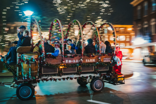 People smile from a decorated carriage as it moves quickly past the camera.