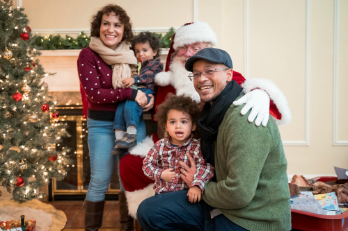 A mother and father each hold one of their children while smiling with Santa Clause