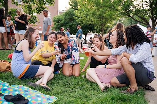 A group of young adults laugh while sitting on the grass, each holding a wine glass or cup of beer