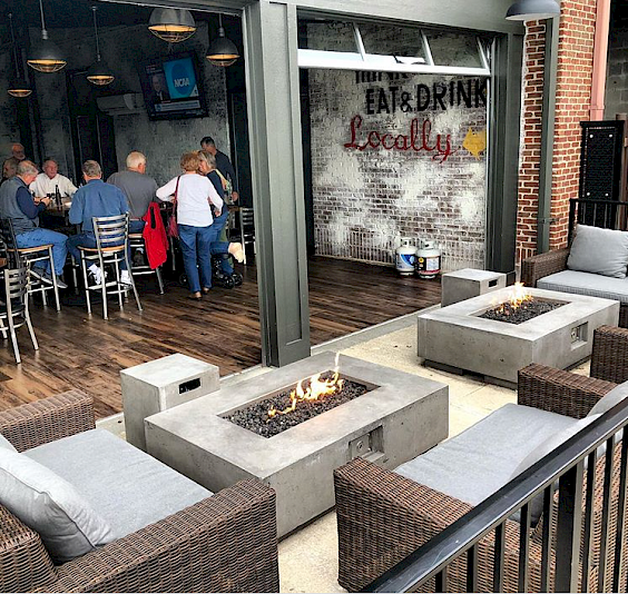 Fire pits ignited in the middle of outdoor seating right outside the Lamplight Room at Gaslight Brewhouse