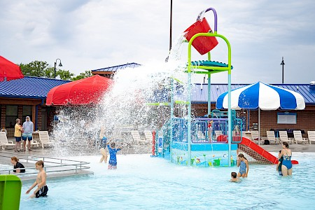 A giant bucket splashes water down onto children in the Aquatic Center pool