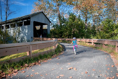 A little girl with a bike helmet rides her bike down a paved path out of the Black Covered Bridge
