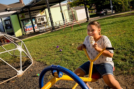 Young girl smiles with an ice cream in her hand while she sits on a teeter tot