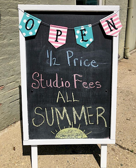 "Chalkboard sign with an OPEN banner across the top and text that says ""half price studio fees all summer"""